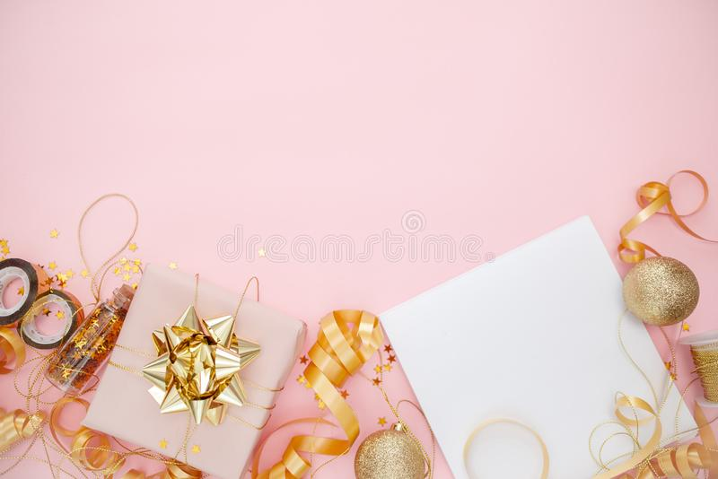 Notebook  with golden bow on pink coral background with stars and sparkles. Festive  and wish list . 2020 New Year concept copyspace top horizontal view stock photo