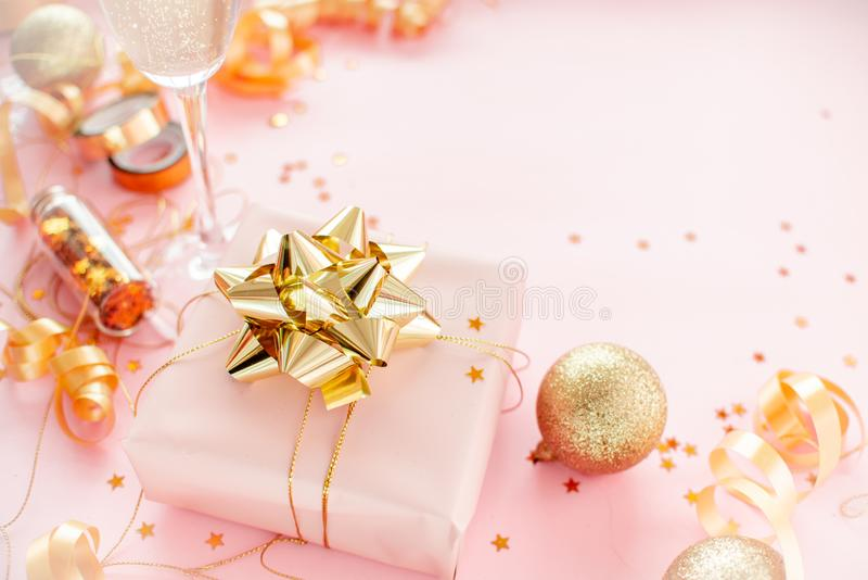 Notebook  with golden bow on pink coral background with stars and sparkles. Festive  and wish list . 2020 New Year concept copyspace top horizontal view royalty free stock photo