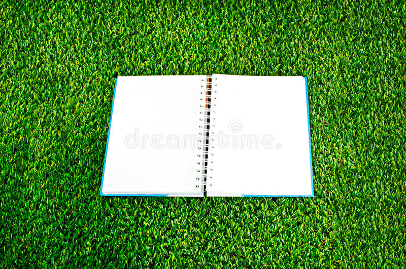 Notebook on green grass background royalty free stock image