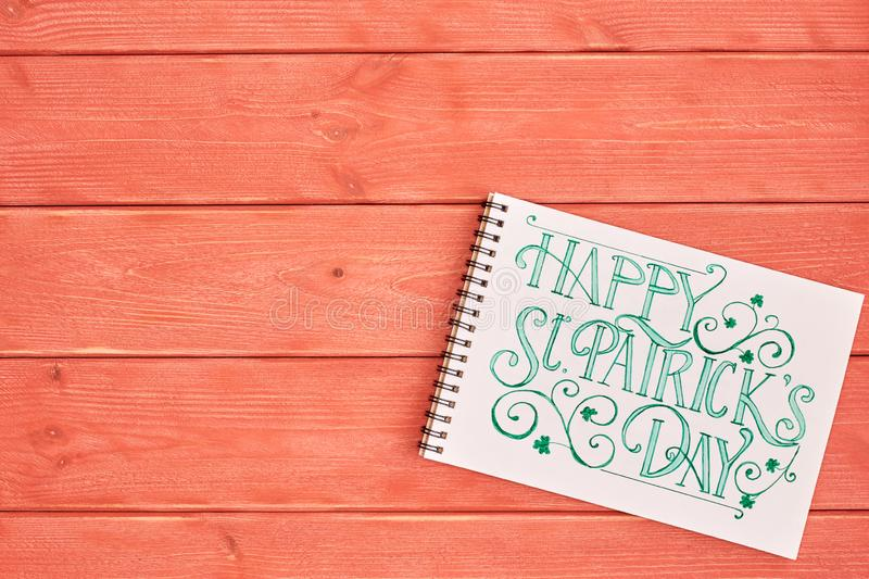 Notebook with green inscription happy Patricks Day, lie on a textured wooden Board, living coral color. stock image