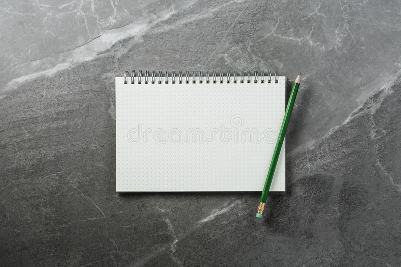 Notebook with green pencil on marble background, top view. Open notebook with green pencil on marble background top view, school notepad on a dark table, office stock photography