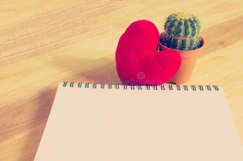 Notebook with heart and cactus on wooden background royalty free stock photos
