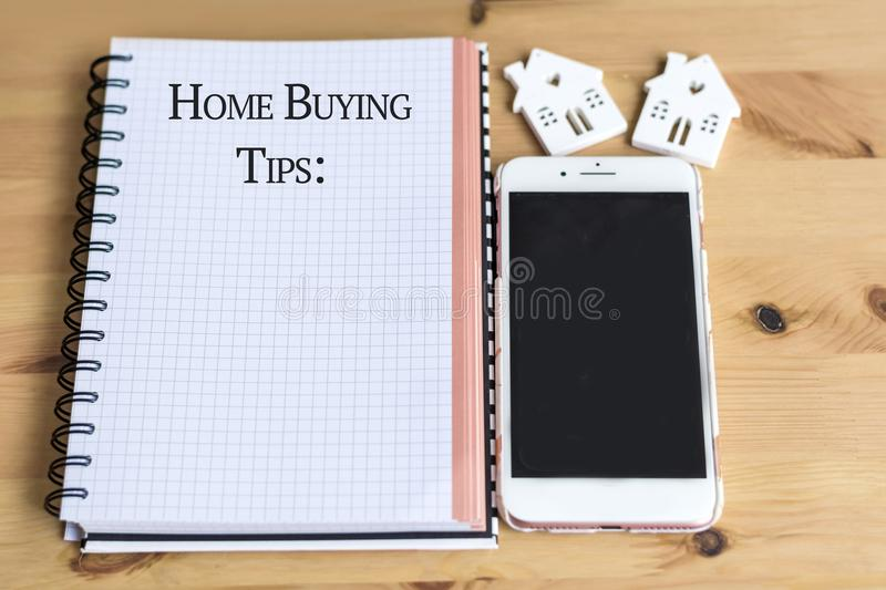 Notebook with Home Buying Tips Text,House Model and phone. Notebook with Home Buying Tips Text,White Wooden Houses Models and Phone royalty free stock photo