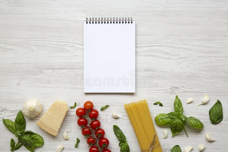 Notebook with ingredients for cooking italian pasta on a white wooden background. Flat lay. Top view. royalty free stock images