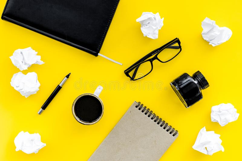 Notebook, ink, dip pen, coffee, glasses for writer workplace set on yellow office background top view mock-up stock images