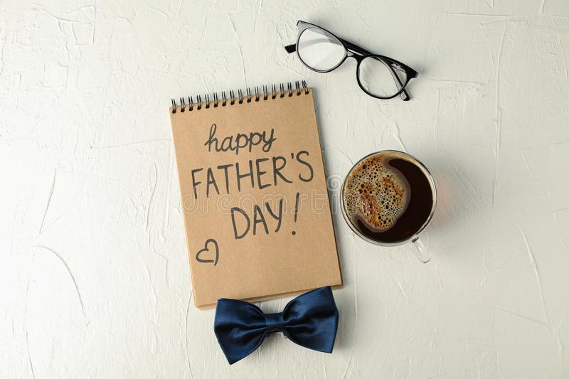 Notebook with inscription happy fathers day, blue bow tie, cup of coffee and glasses on white background, space for text royalty free stock photo