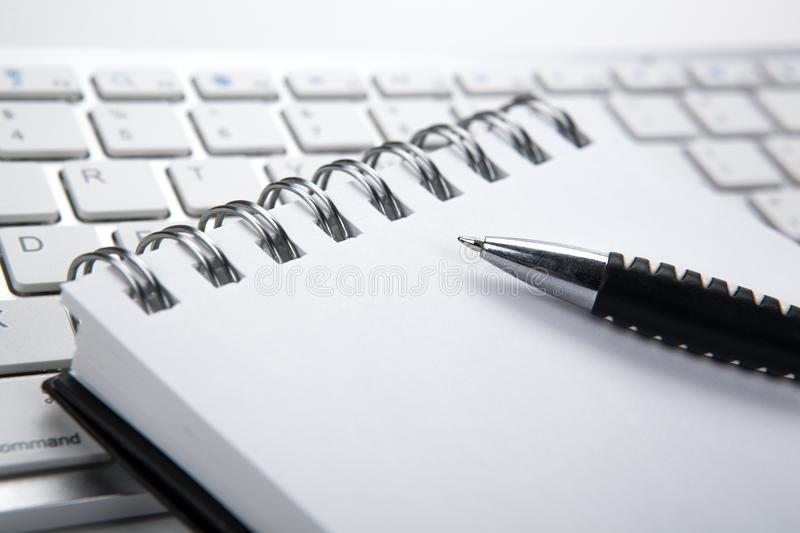 Business still life of a notebook and keyboard on the desktop. Notebook and keyboard on the desktop closeup stock photo