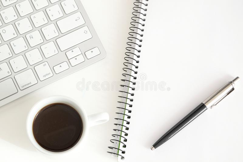Notebook and keyboard next to a cup of coffee on a white desktop. Home working concept stock photos
