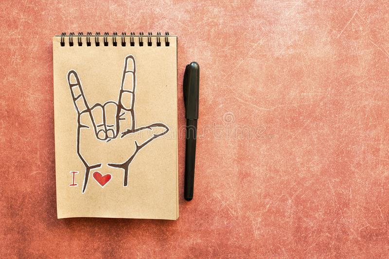 Notebook of Kraft paper, with a painted ASL American sign language symbol I Love you ILY. Suitable for congratulations to the stock photo