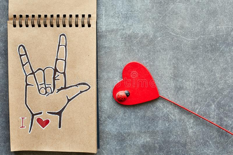 A notebook of Kraft paper, with a painted ASL American sign language symbol I Love you ILY and a wooden red heart with a small stock image