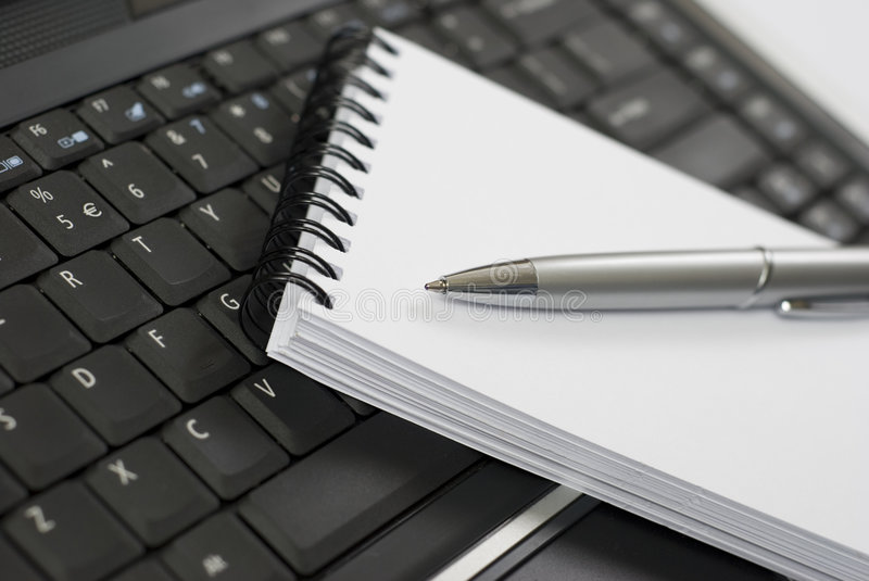Notebook and laptop. A paper notebook with a pen on a laptop computer keyboard