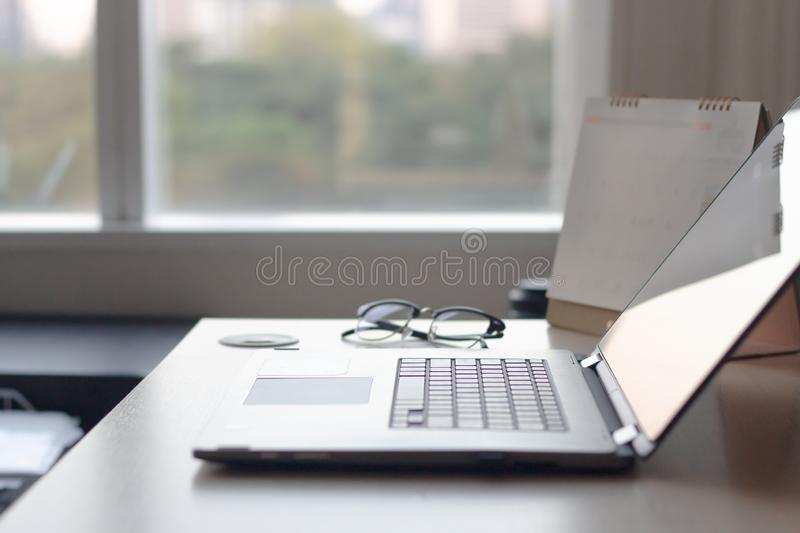 Notebook laptop in desk table in office windows and city view. stock photo