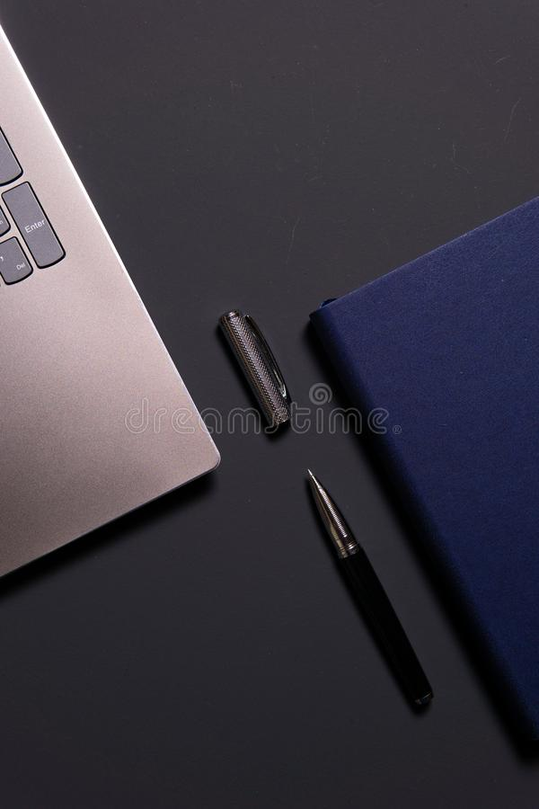 Notebook, laptop, glasses and pen on the table royalty free stock images
