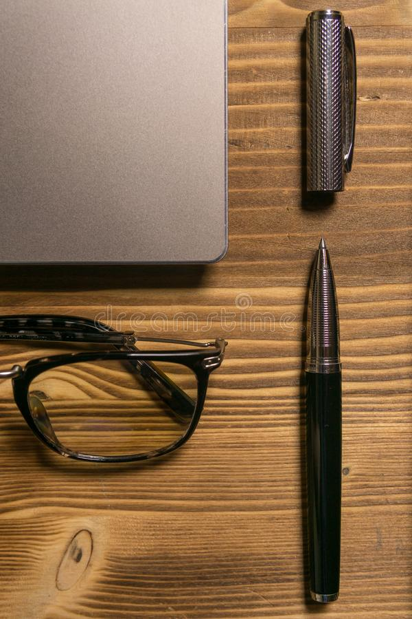 Notebook, laptop, glasses and pen on the table stock photos
