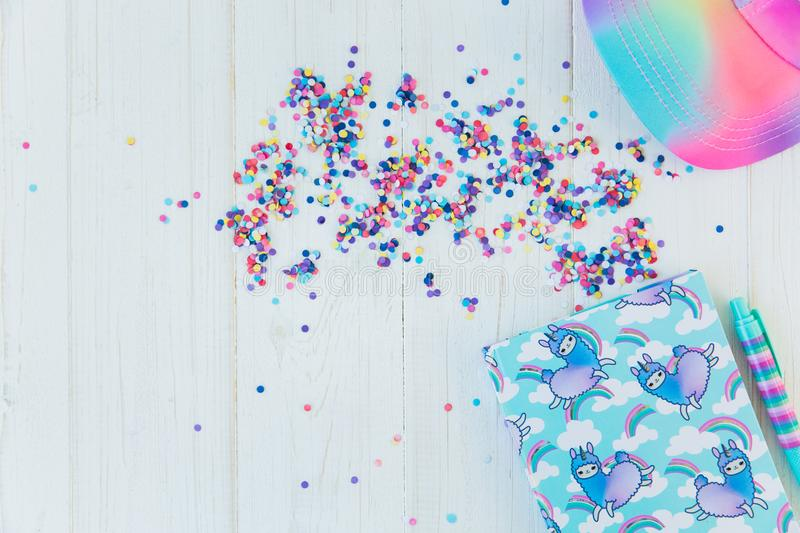 Notebook with llama unicorn and rainbow with colorful gel pen and rainbow cap on white wooden background with confetti. Idea of Girly Desk table. Back to royalty free stock photos