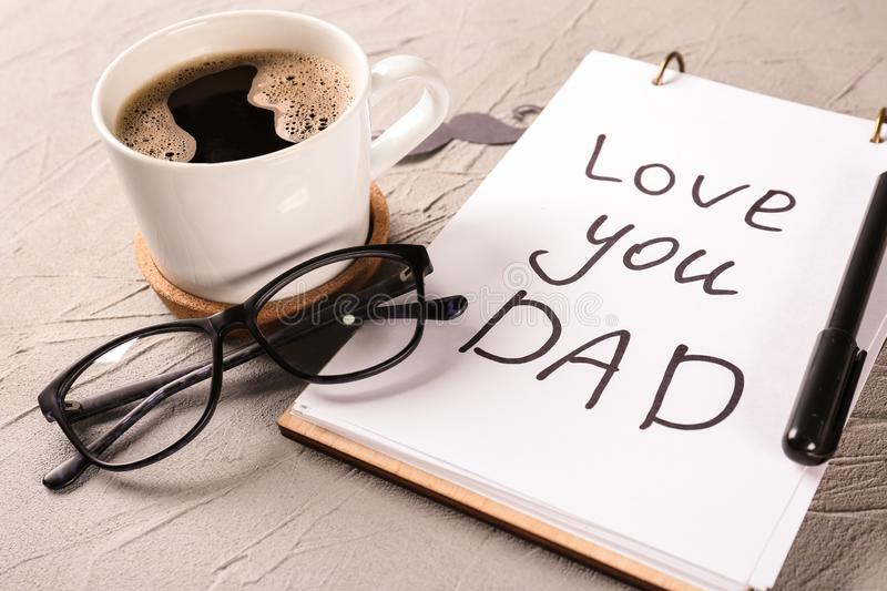 Notebook with LOVE YOU DAD inscription, cup of coffee and glasses on grey textured background. Happy Father's Day celebration royalty free stock photo