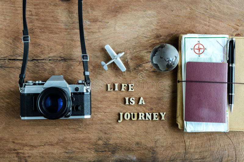 Notebook with map, passport and camera on wooden background. With word Life is a journey stock photography