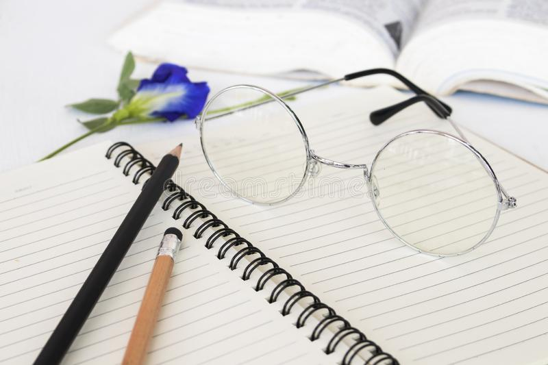 Notebook memo ,dictionary book and spectacle of student for study. Arrangement flat lay style on background white royalty free stock image