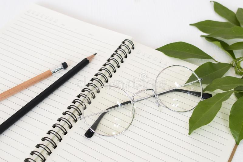 Notebook for memorandum with pencil ,spectacles. Arrangement flat lay style on background white wooden royalty free stock photo