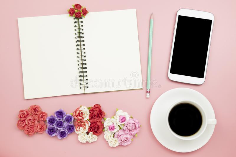 Notebook mobile phone black coffee flower rose on pink background pastel style with copyspace flatlay topview. Notebook mobile phone black coffee flower rose on stock image