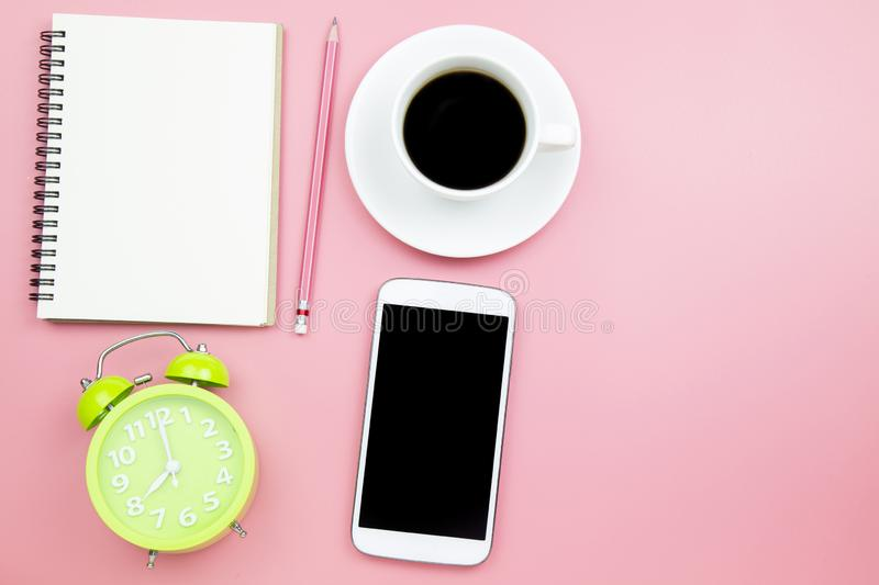 Notebook mobile phone black coffee green clock on pink background pastel style with copyspace flatlay topview. Notebook mobile phone black coffee green clock on royalty free stock photography