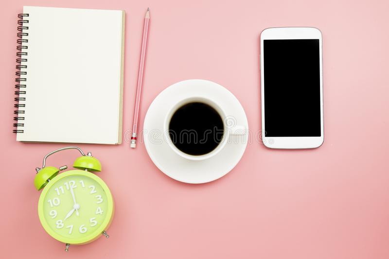 Notebook mobile phone black coffee green clock on pink background pastel style with copyspace flatlay topview. Notebook mobile phone black coffee green clock on royalty free stock photo