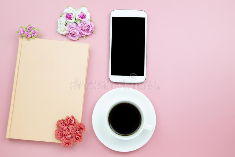 Notebook mobile phone and black coffee white cup on pink background pastel style with copyspace flatlay topview. Notebook mobile phone and black coffee white stock image