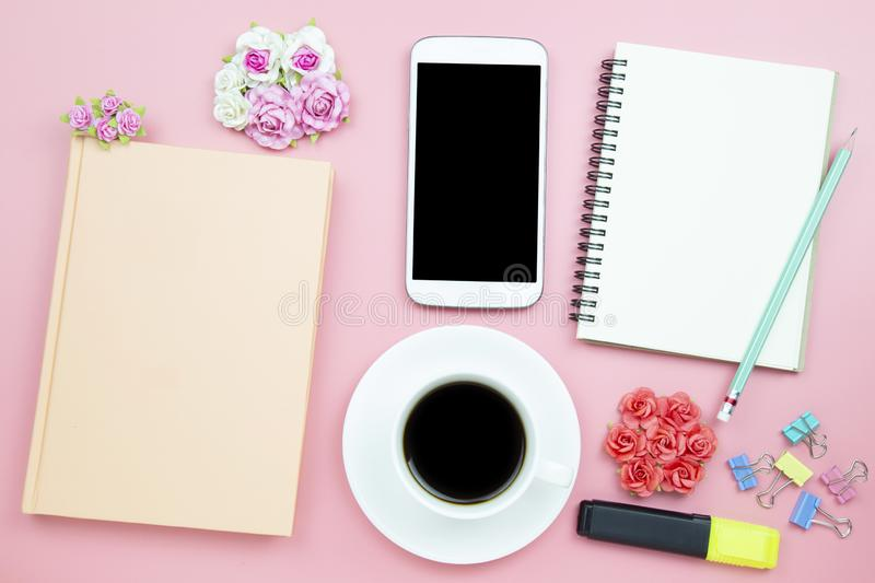 Notebook mobile phone and black coffee white cup on pink background pastel style with copyspace flatlay topview. Notebook mobile phone and black coffee white royalty free stock photo