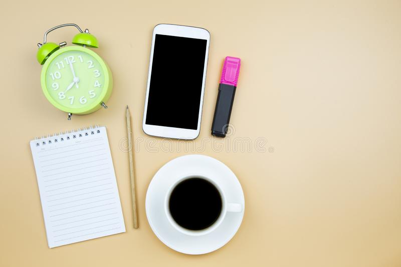 Notebook mobile phone calculator and black coffee white cup green clock on orange background pastel style with copyspace flatlay royalty free stock photo