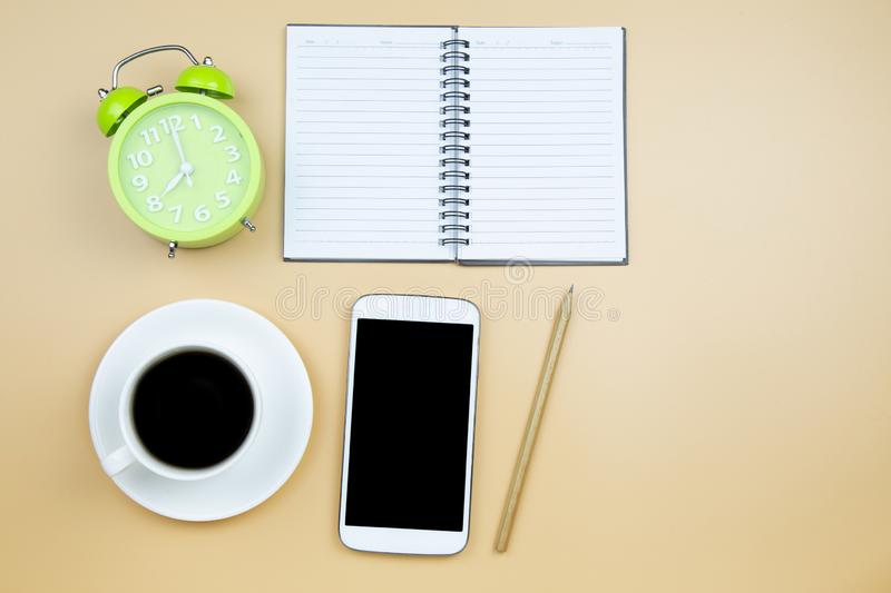Notebook mobile phone calculator and black coffee white cup green clock on orange background pastel style with copyspace flatlay stock photos