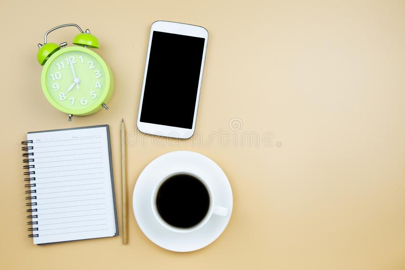 Notebook mobile phone calculator and black coffee white cup green clock on orange background pastel style with copyspace flatlay. Notebook mobile phone stock image