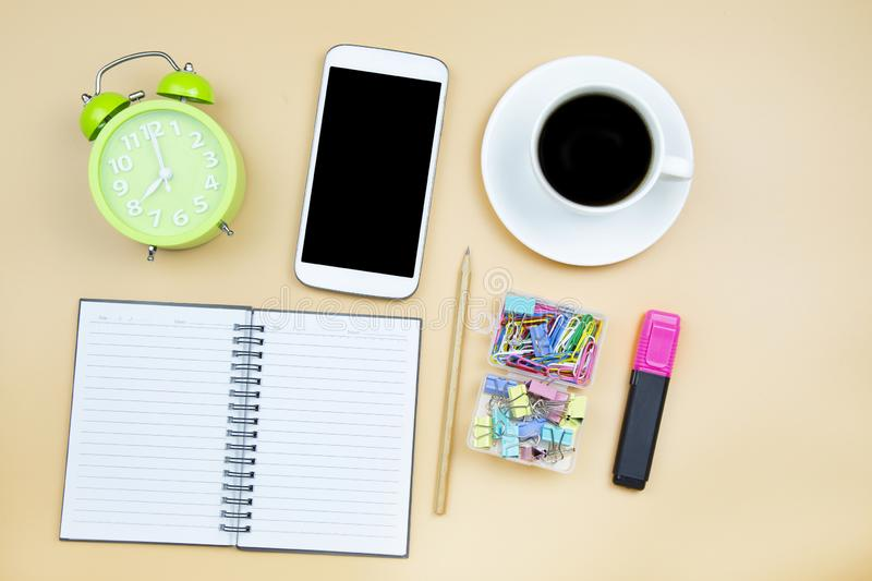 Notebook mobile phone calculator and black coffee white cup green clock on orange background pastel style with copyspace flatlay royalty free stock image