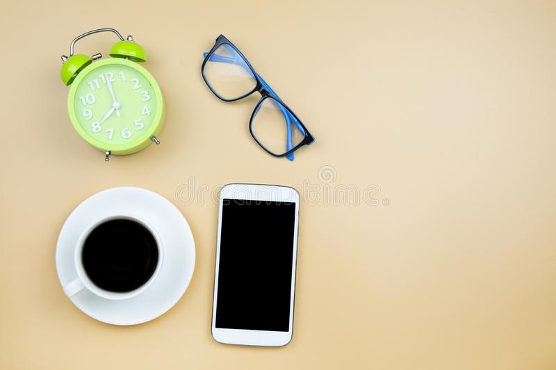 Notebook mobile phone calculator and black coffee white cup green clock on orange background pastel style with copyspace flatlay royalty free stock photos