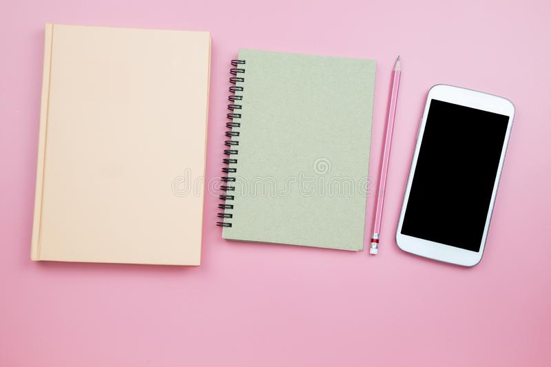 Notebook mobile phone on pink background pastel style with copyspace flatlay topview. Notebook mobile phone on pink background pastel style with copyspace royalty free stock photography