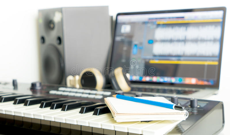 Notebook and Music Keyboard on Music studio desktop for song writer. Notebook and Music Keyboard on Music studio working desktop for song writer stock image
