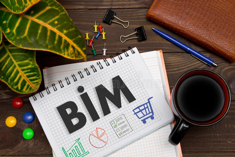 Notebook with a notes BIM on the office table with tools. Concept with elements of infographics. royalty free stock photography