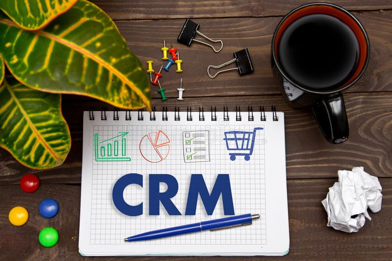 Notebook with a notes CRM on the office table with tools. Concept with elements of infographics. royalty free stock photography