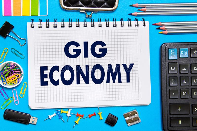 Notebook with Notes GIG ECONOMY office tools on a blue background . Concept GIG ECONOMY.  stock image