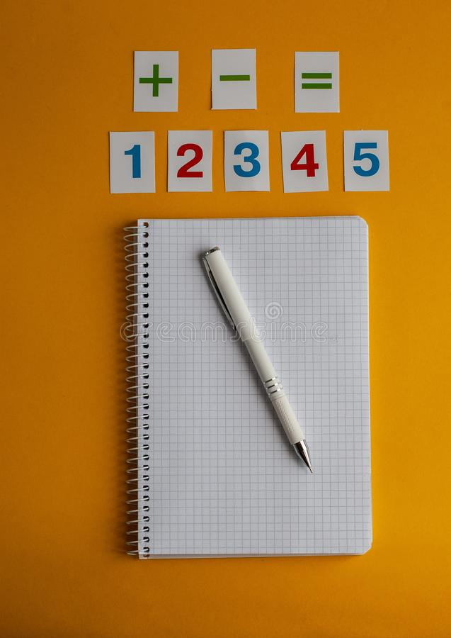 Notebook, numbers, white pen on a yellow background. Accessories for study. Mathematics, geometry, algebra. Top view, flat lay, copy space royalty free stock photos