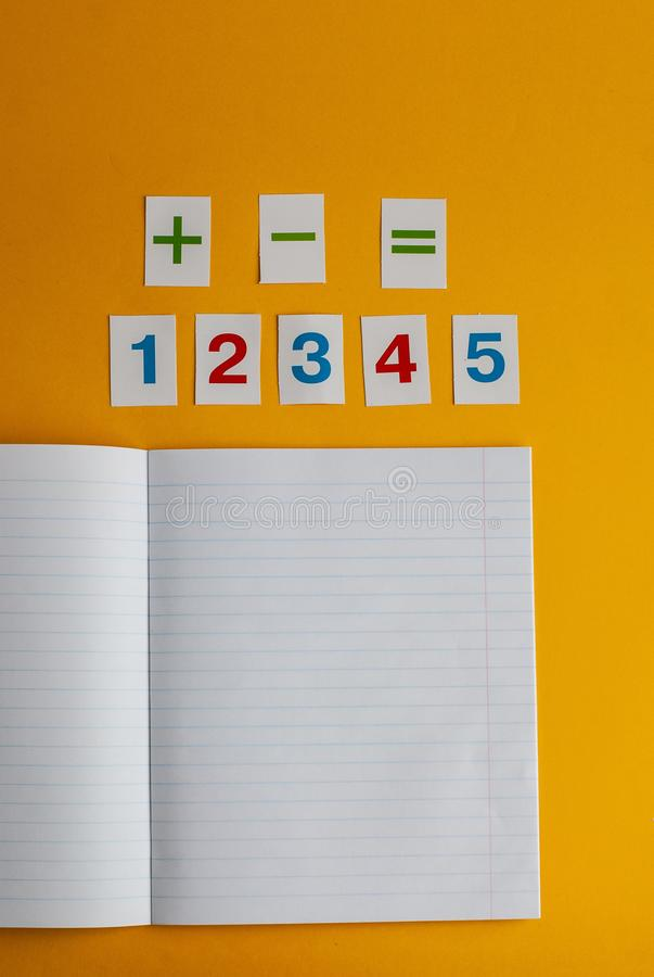 Notebook, numbers on a yellow background. Accessories for study. Mathematics, geometry, algebra. Top view, flat lay, copy space royalty free stock images