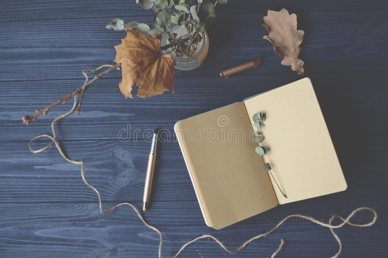 Notebook and objects of decoration on the wooden desk. Inspirational vintage workplace. royalty free stock photos