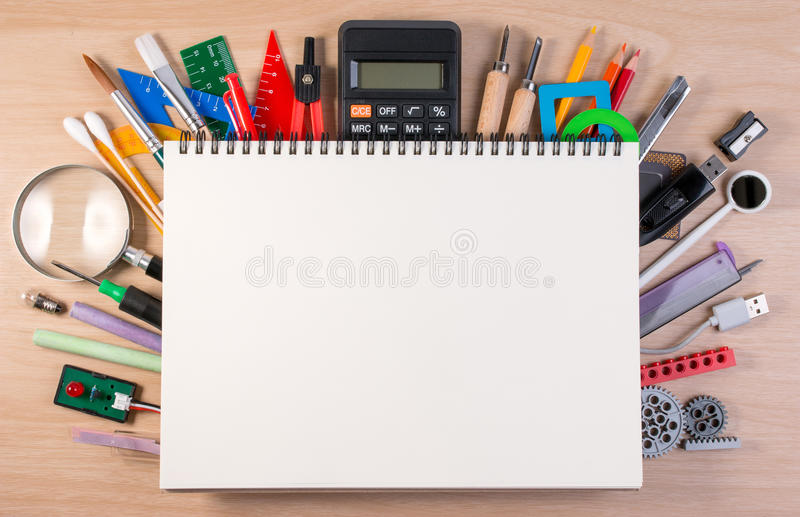 Notebook over school supplies or office supplies on school table. Background with school or office material with copy space for text stock photo
