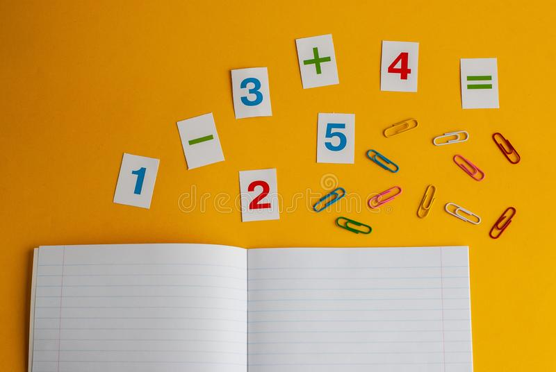 Notebook, paper clips, numbers on a yellow background. Accessories for study. Mathematics, geometry, algebra. Top view, flat lay, copy space stock photos