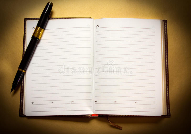 Notebook and pen. On a golden background royalty free stock photos