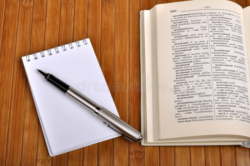 Notebook with pen. And old Russian-German dictionary stock photography