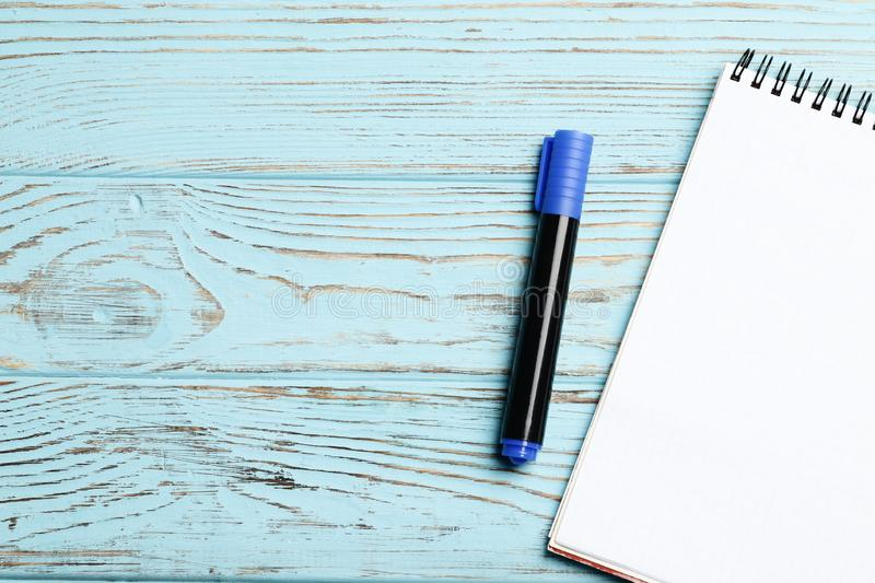 Notebook and pen on the blue wooden background. Place for text. stock image