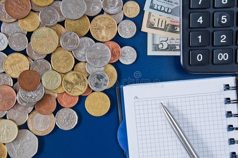 Notebookwithapen, calculator, lijstÂmoneyandvariouscoinsontheroyalty-vrije stock afbeeldingen