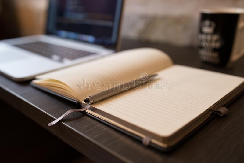 Notebook and pen on desk with computer stock images