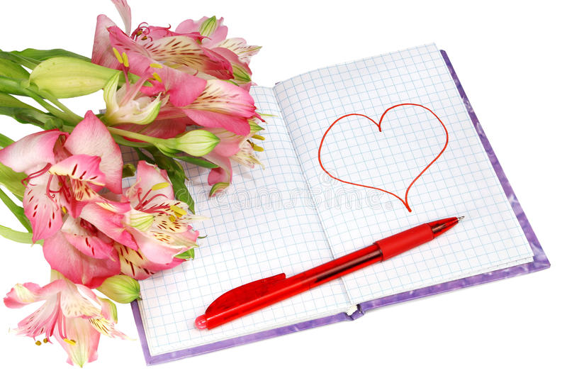 Notebook with a pen by flowers and heart. Isolated on white background royalty free stock photos