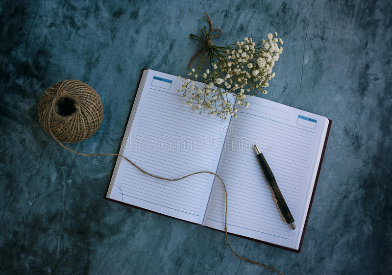 Notebook, pen and flowers stock image